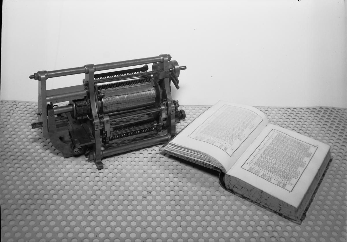 Differensmaskin avsedd för automatisk beräkning och tryckning av matematiska tabeller (logaritmtabeller, potenstabeller, kvadrat- och kubikrötter). Tillbehör: Låda till förvaring.