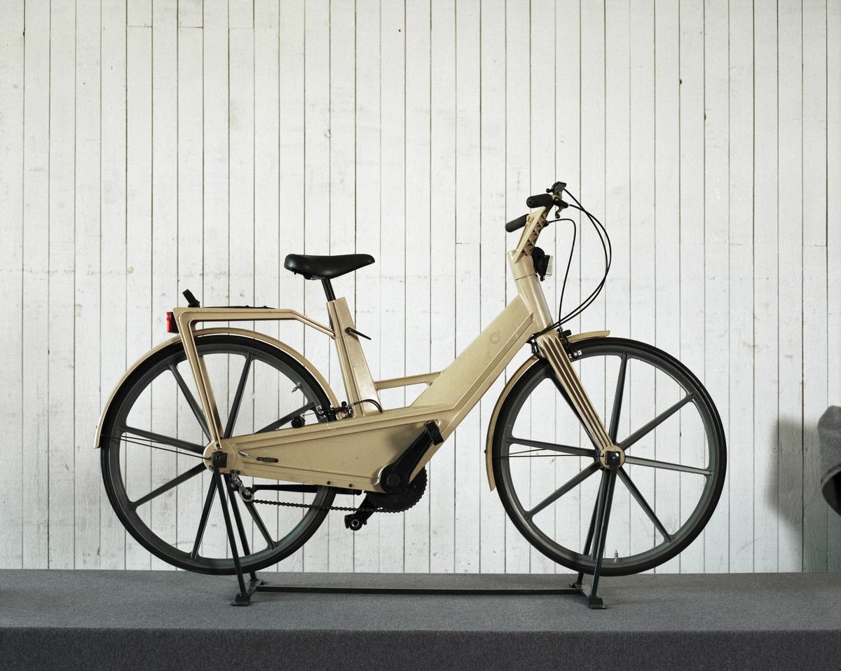 Treväxlad cykel, Iteras normalmodell.   Ram, gaffel hjul och vevparti är tillverkade i kompositplast - här en kombination av termoplast och glasfiber. Hjul med åtta ekrar, också i kompositplast. Sadel i konstläder, däck och slangar av gummi.