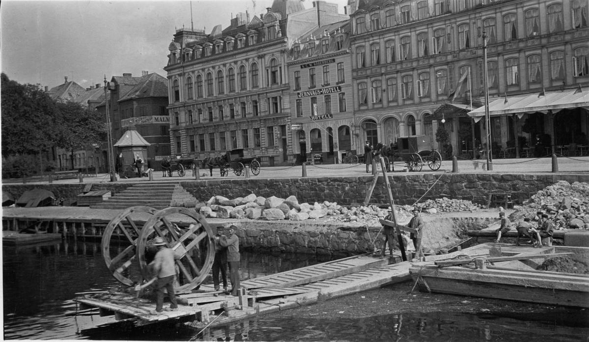 Handdriven grävmaskin i arbete i Malmö hamn. Använd till 1914. Konstruktion från 1770-talet. I bakgrunden skymtar Jernvägs-Hotellet. (Bilden är publicerad i Daedalus 1941).