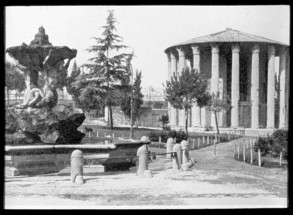 Skioptikonbild från institutionen för fotografi vid Kungliga Tekniska Högskolan. Motiv föresällande Hercules Victortemplet i Rom, Italien. Bilden är troligen tagen av John Hertzberg under en resa i Europa och är en tryckt bild av ett fotografi.