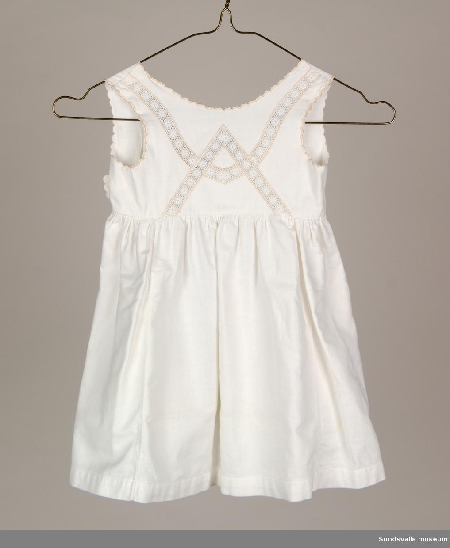 Ärmlös flickklänning i vit bomull med infälld spets och kantbrodyr.