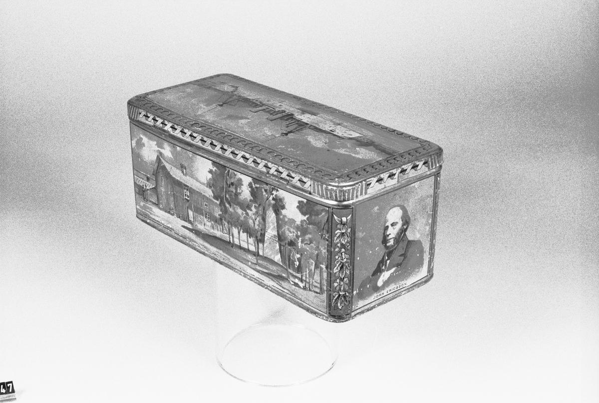 """Cigarrlåda av bleckplåt med bilder i färglitografi ur John Ericssons liv och likfärd till Stockholm. Lådan har innehållit 200 cigarrer """"Colorado Claro""""."""