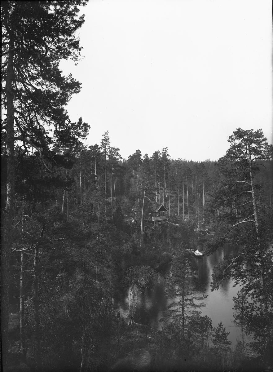 Fönsterbild med motiv av hytta i skogslandskap vid sjö, möjligen i Hedemoratrakten.