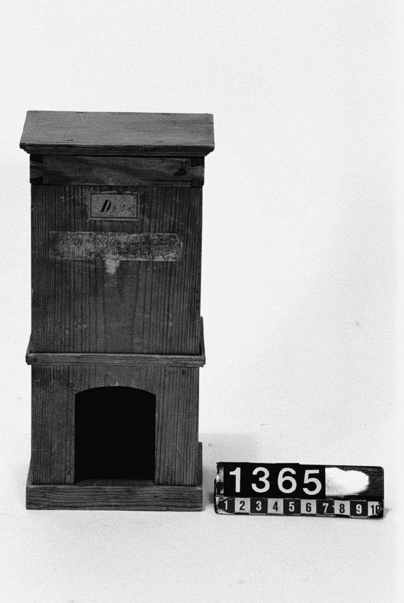 """Modell av kamin och spis. Text på föremålet: """"N:o 211. Modell på en Kamin och Spisel med 4 rör. D.b.B.4. i Tab. I.b."""" Etiketten delvis otydbar vid inv. jan-96."""