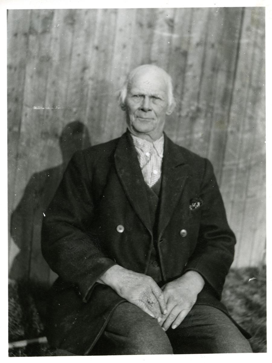 Portrett i halvfigur av eldre mann iført jakke bukse og rutete skjorte. Han sitter ute foran en vegg.
