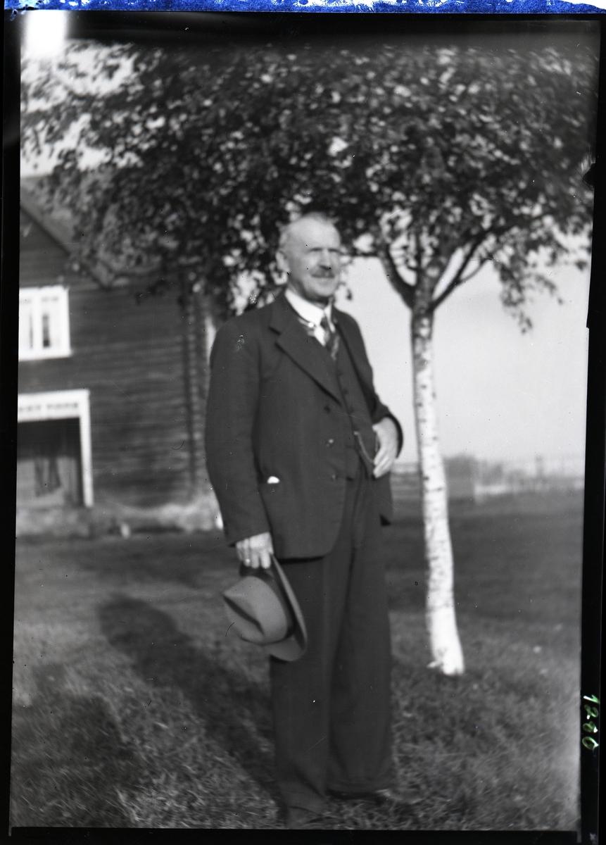 Portrett av eldre mann i helfigur. Han er kledd i dress og har en hatt i hånden. Bildet er tatt under et tre, utenfor et hus. Amerika?