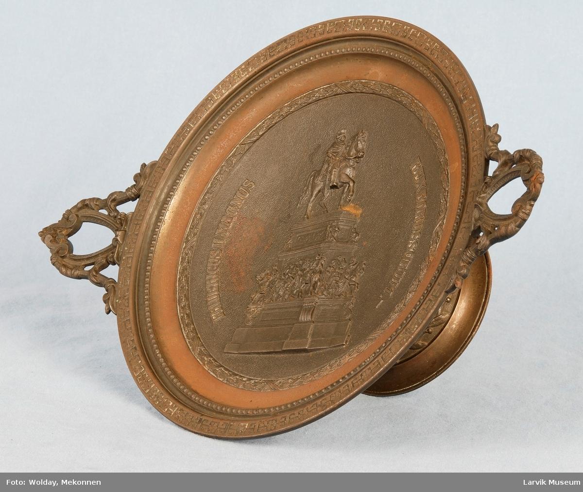 """rytterstatue + buet opphøyet tekst på hver side av hovedmotivet:""""FRIDERICUS II MAGNUS"""",(vs);""""REX BORUSSORUM.-"""",(hs). tre kantinger rundt hovedmotivet:innerst rundt hovedmotivet en (laurbær-)krans, videre utover en med perlestav og ytterst en med regelmessig gjentatte geometriske mønstre. fint dekorerte hanker, åpningen i midten av disse har form av et skjold. bladbord på foten av fatet rundt stet"""