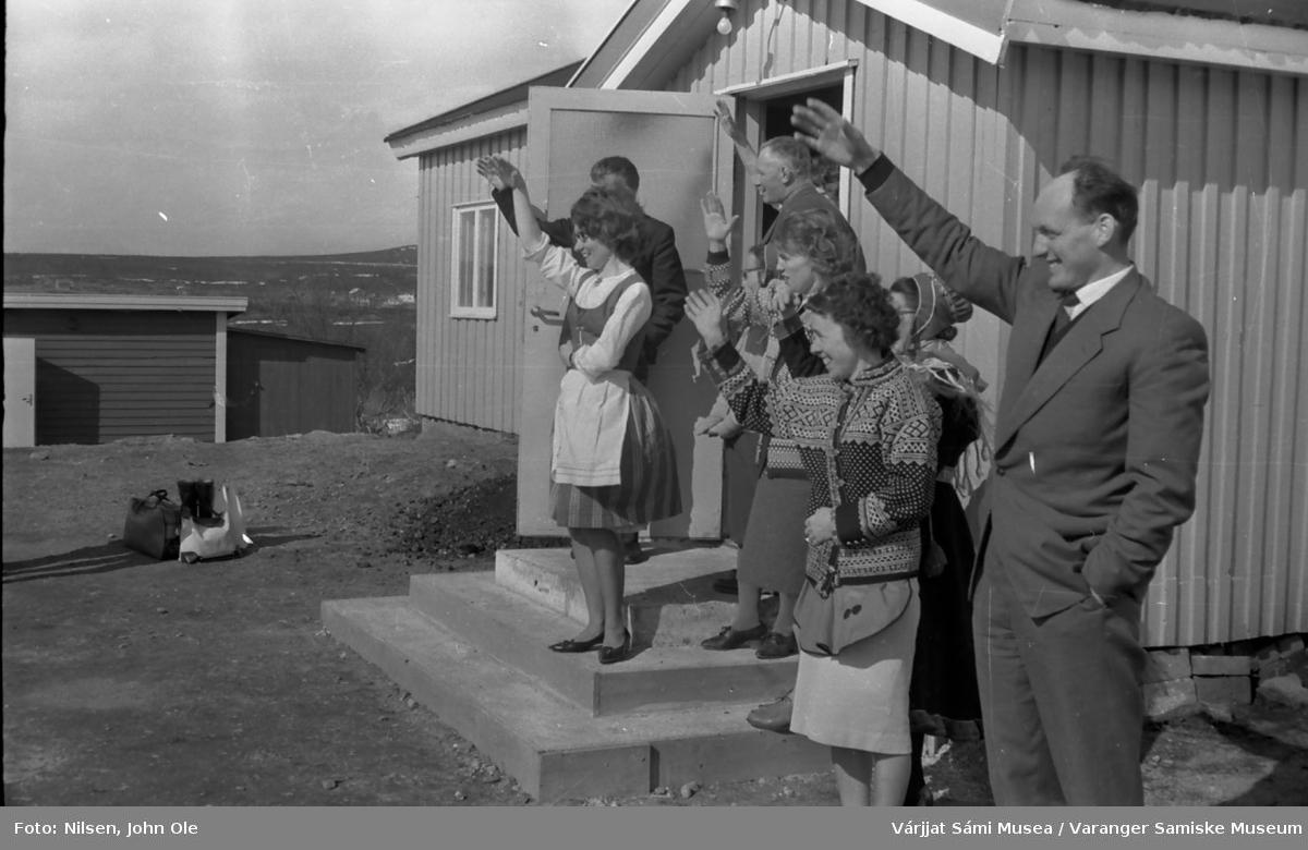 Menn og kvinner står på trappen på Soltun forsamlingshus på Vesterelvnesset og vinker farvel. Mannen midt i døråpningen er Reidar Bønå, Signe Nilsen med kofte og Einar Hagalid helt til høyre. 30. mai 1966.
