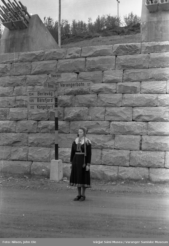 Signe Nilsen står ved brohodet på østsiden av Tana Bru. Bak henne står det et skilt som viser distansen til ulike steder i Øst-Finnmark. 26. juni 1966.