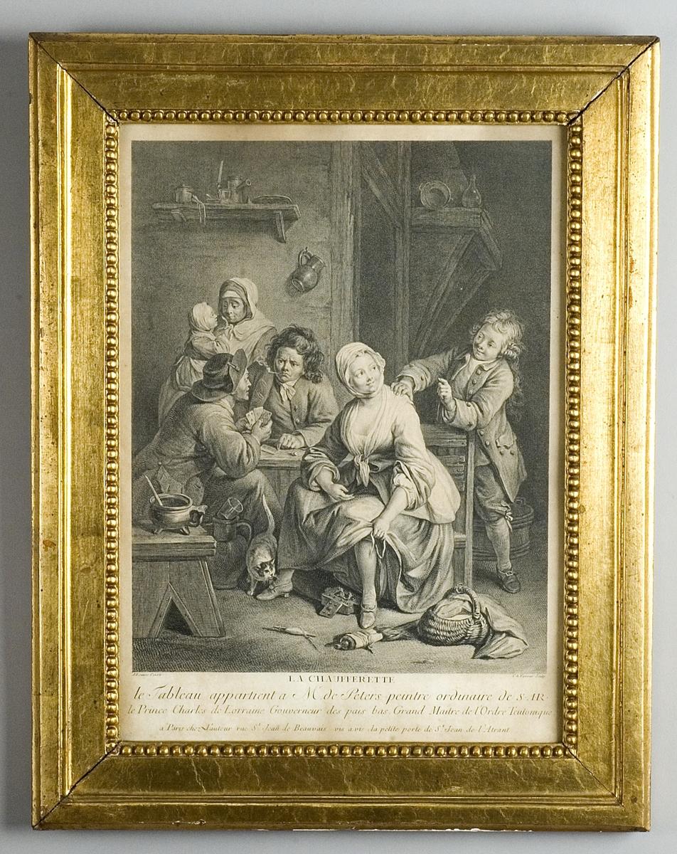 Interiör med en sittande kvinna som värmer sig vid en glödpanna, två kortspelande herrar, en ung man samt i bakgrunden en kvinna och ett barn samt en katt.