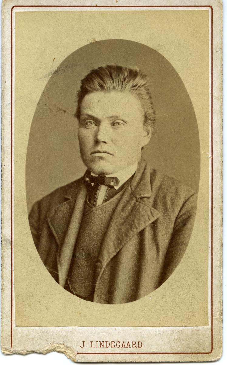 Portrett av en mann. Mannen er iført skjorte og vest med frakk over. I halsen har han halspynt.