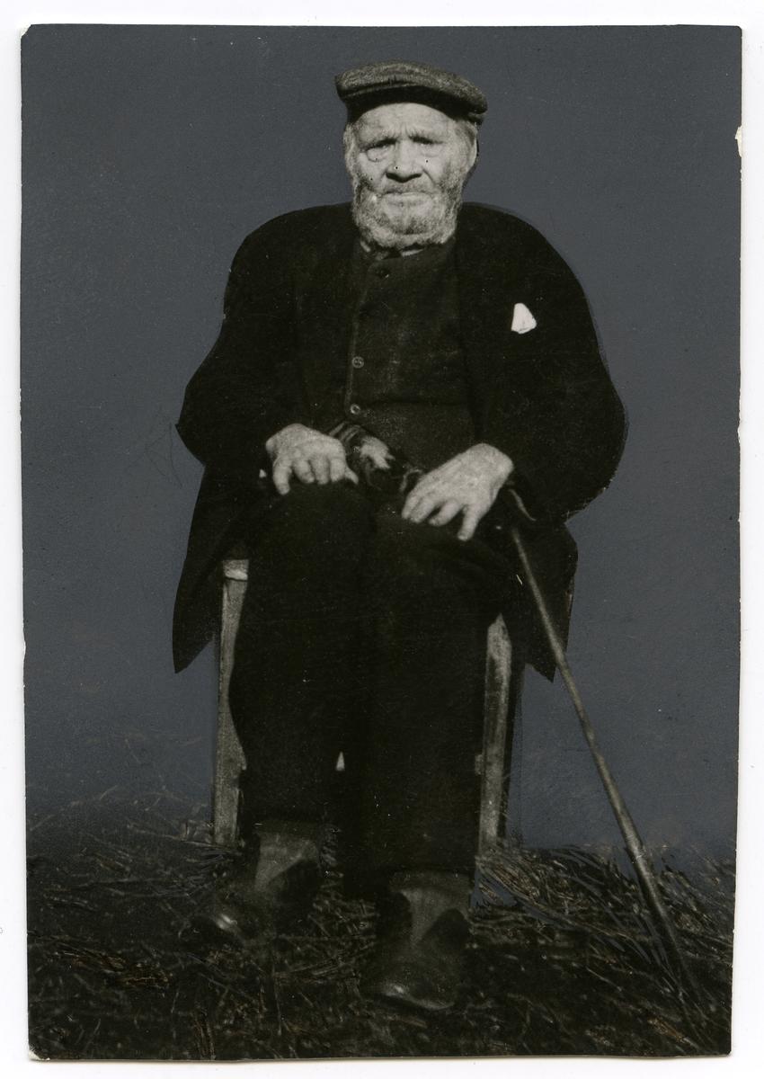 Portrett av en eldre mann sittende på en stol. I hånden har han en stokk. Mannen er ikledd en hatt på hodet og mørk dress. I lommen på jakken er det et lommetørkle.