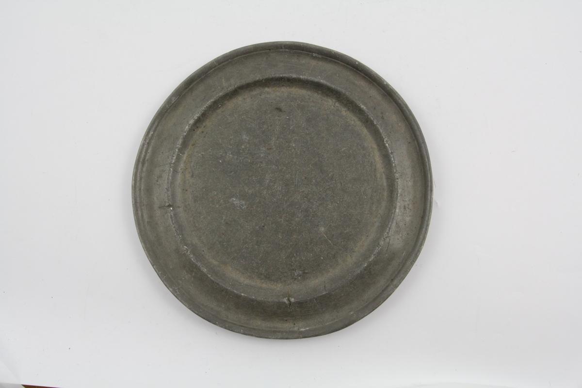 Flat, tinn, sirkelrund, kanten har opphøyet rand og er prydet med gravert linje. Flere utviskede stempler på tallerkenens bakside.