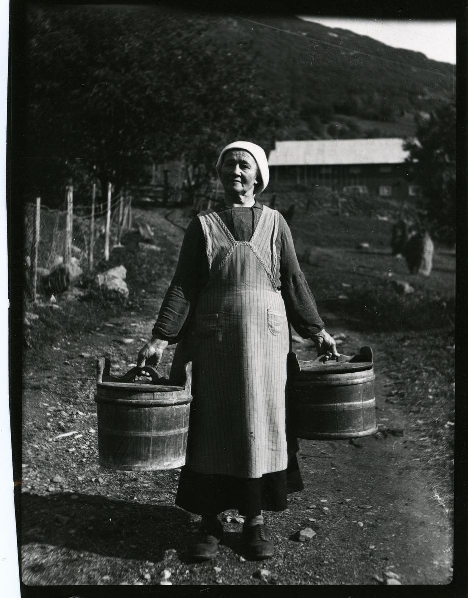 Kvinne med trebutt. Hun er ikledd skaut og kjole med overkjole.