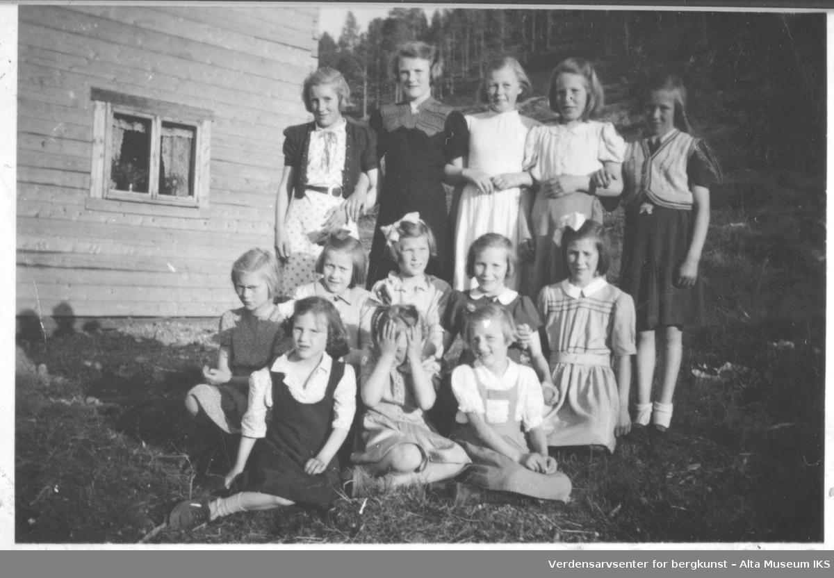 Gruppebilde med 13 jenter utenfor trebygning. Sommer.