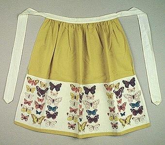 Midjeförkläde i grönt bomullstyg med ett påsytt tyg med tryckta, färgglada fjärilar på vit botten, indelat till tre fickor, Knytband 140 cm.