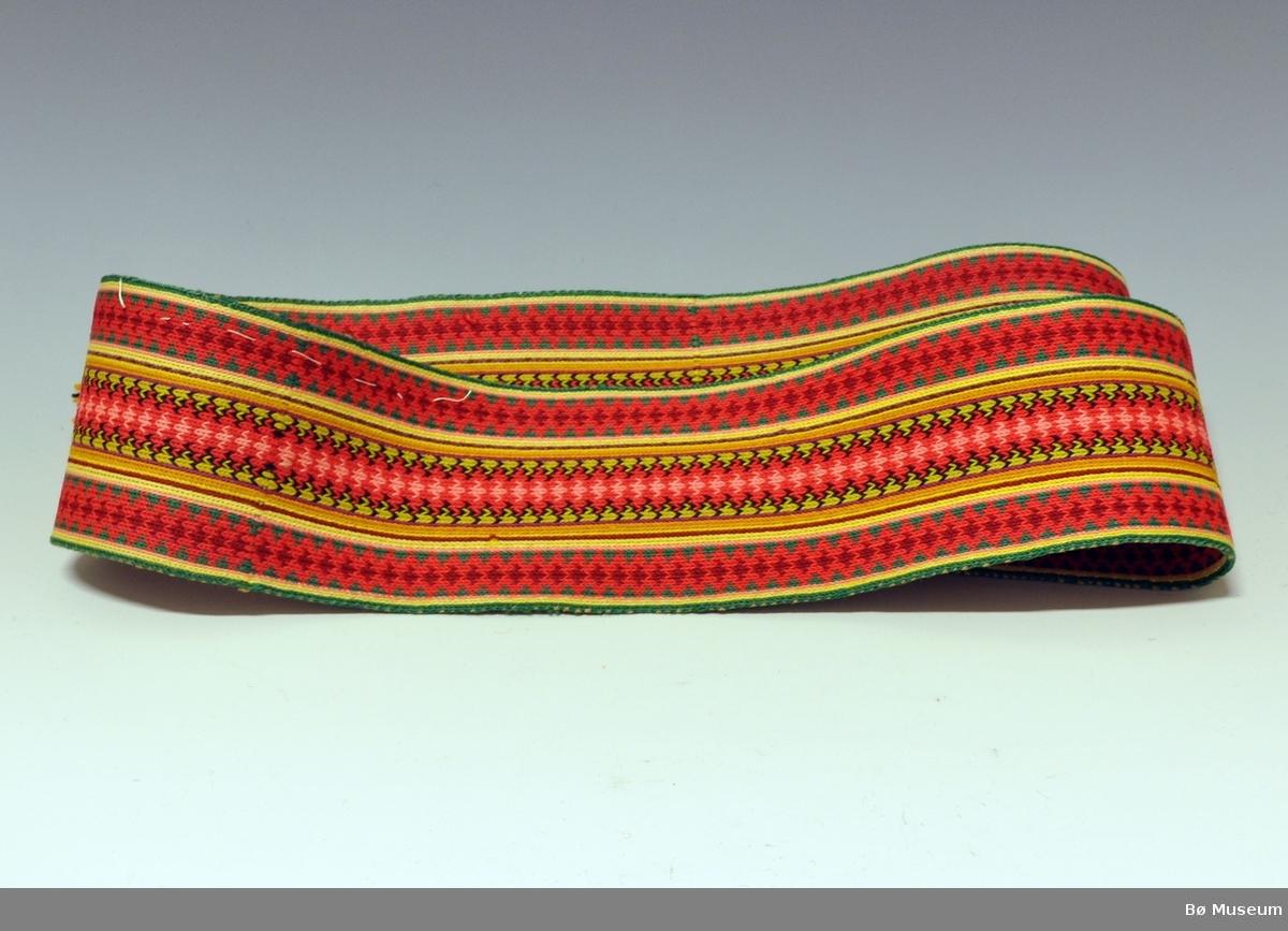Brikkevevd belte med frynser i ene enden, den andre enden ser ut til at beltet er skåret av. På ene siden er det montert to metallhekter og sydd på to hemper i knepphullssting.Beltet er vevd i ca. 9 farger.