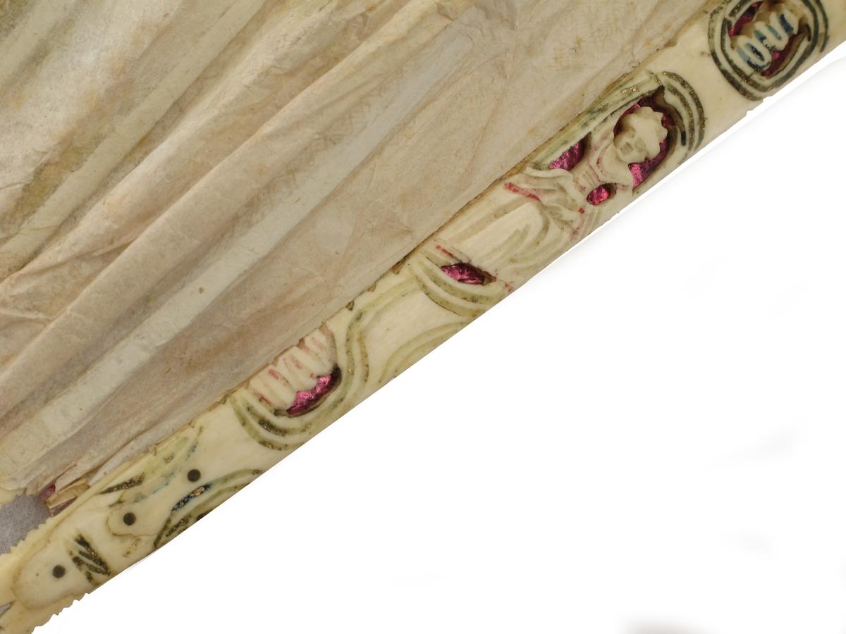 Vifte av papir, tyll og elfenben. I for dårlig tilstand til å måles utslått. På bunnpapiret er limt endel utklipp av kobberstikk. Grunnfargen er hvit med dekor i opprinnelig sterke, nå sterkt falmede  farger. En del  enkle utskjæringer i elfenbenet.