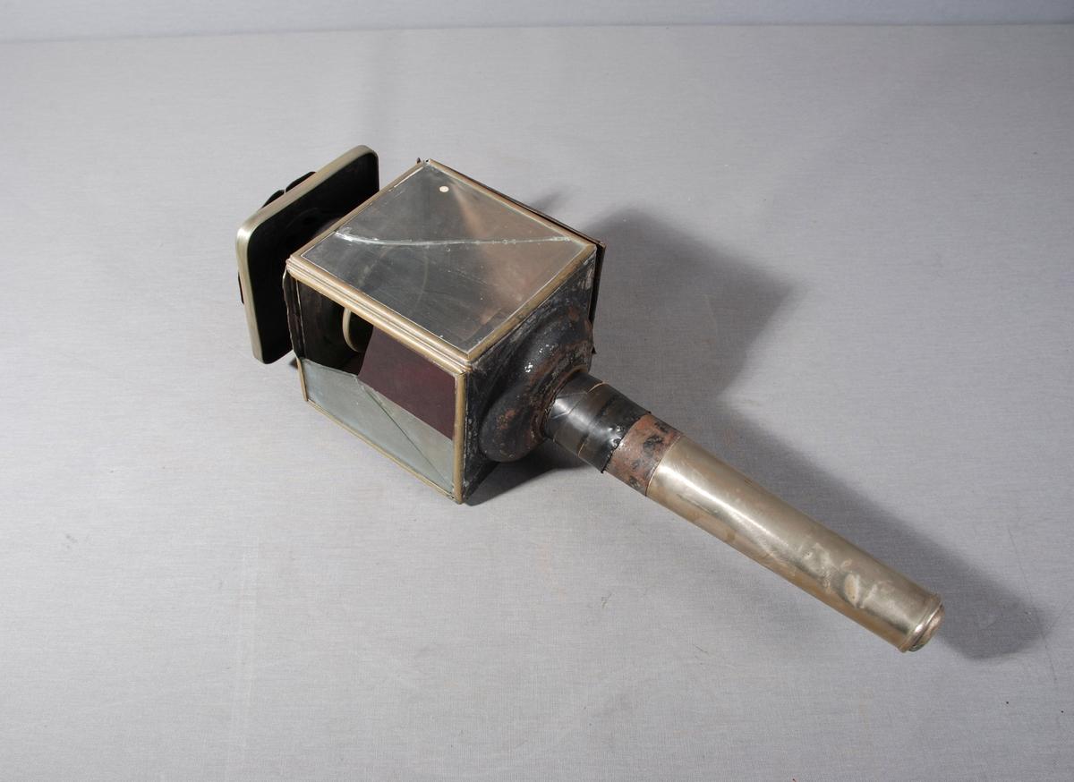 Olje-/stearinlyslykt til bruk på hestevogn eller slede. Firkantet lyktehode på metallrør. Øverst hatt for utlufting. Lyktehodet kan åpnes ved at ene siden av metall er hengslet. En side er av rent metall og to sider er av glass, det ene fasettslipt. Innvendig base for brenner.
