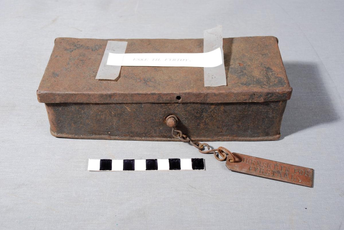 Rektangulært skrin fir syrstål, hengslet lokk. Skrinet har to rom. Knott på fremsiden der det er festet en kjetting med metallmerke med tekst.