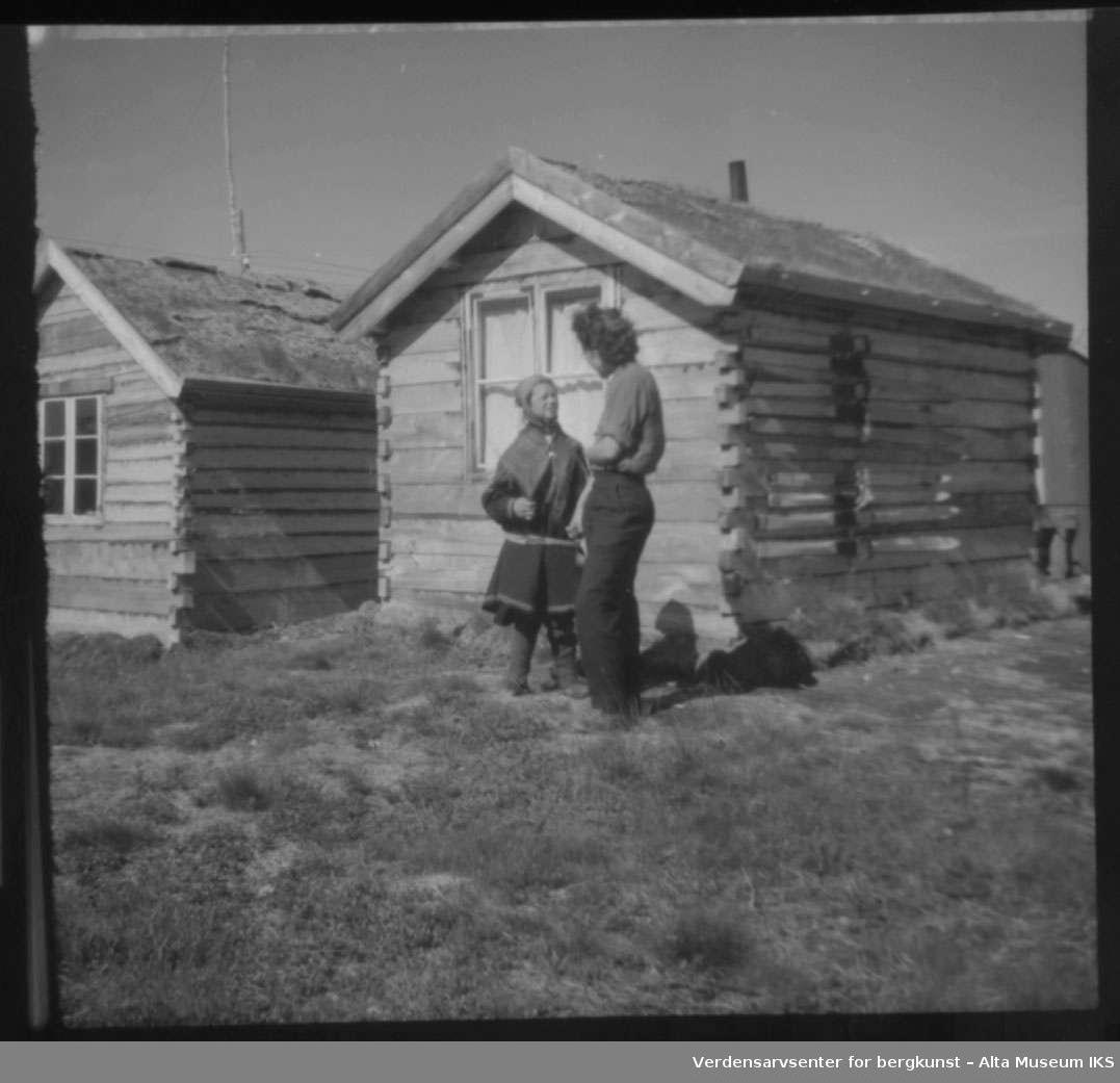 Tømmerhus i bakgrunnnen,  to kvinner står og samtaler foran den. Den ene kvinnen er kledd i kofte.