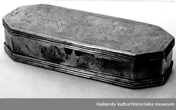 Åttakantig dosa med fällock. På locket graverat en grav, figurer och ornament.