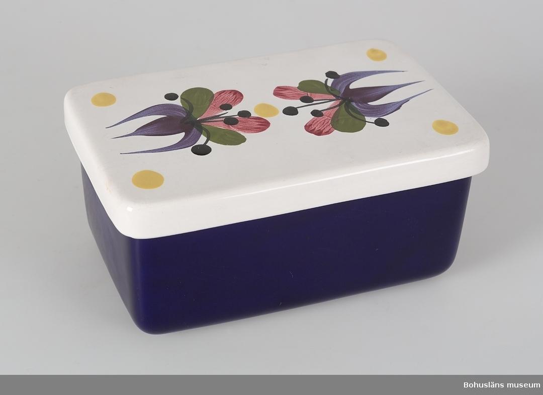 """Rektangulär. Blank blå-lila glasyr på asken. Blank vit glasyr på locket med dekor; gula prickar - en i varje hörn och en i mitten samt två blommor i lila, grönt, rosa och svart. Under botten står det """"SYCO SWEDEN"""". Denna typ av ask var populär i England."""