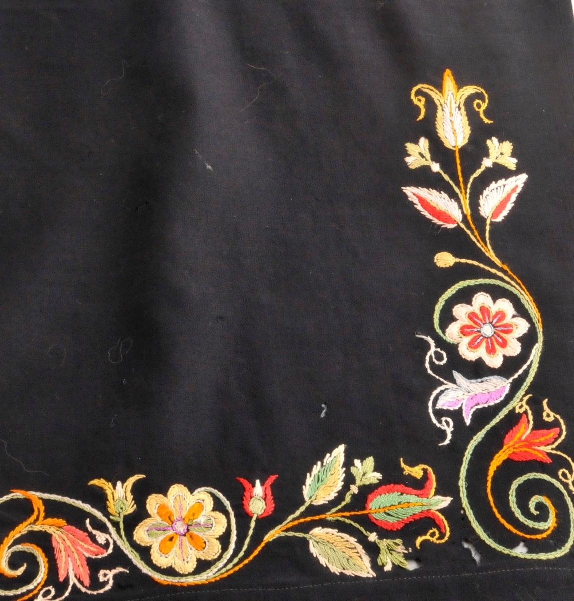 Svart stoffstykke/forkle brodera med blomsterrankar rundt kantane nede. Brodera med ikatfarga garn i silke.Det er ikkje kanta, men er falda oppe og nede. Jarekant på begge langsidene. Ber preg av å ha vore i bruk.