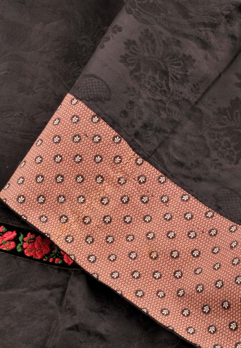 """Forkle i svart silkedamsk, med  blomstermotiv. Sydd saman av to stoffbredder med handsaum midt på forkledet. Tre legg på kvar side oppe.. Kanta for hand med blomstrete bomullsstoff (kattun) langs kanten nede på vranga, denne kanten er vrangsydd slik at litt av den er synleg frå rettsida. Lintrådrestar nederst på forkledet, truleg er dekorband blitt spretta av då dette tradisjonellt var vanleg på slike forkle. Det er restar av to ulike trådtyper på rettsida nede på forkledet, Det er òg restar av tråd langs kanten heilt nederst på vranga, så forkledet har truleg vore kanta med to eller tre band eller stoff. I tillegg er det trådrestar kring begge sidene og øverst opp på forkledet. Nede i hjørnene er det trådrestar som dannar ein litt breiare """"kant"""", lik den som ein ser nederst på rettsida av forledet. Øverst er forkledet kasta over med grove kastesting. Jarekant langs begge langsidene og langs saumen på midten. Sydd saman på midten med maskin."""