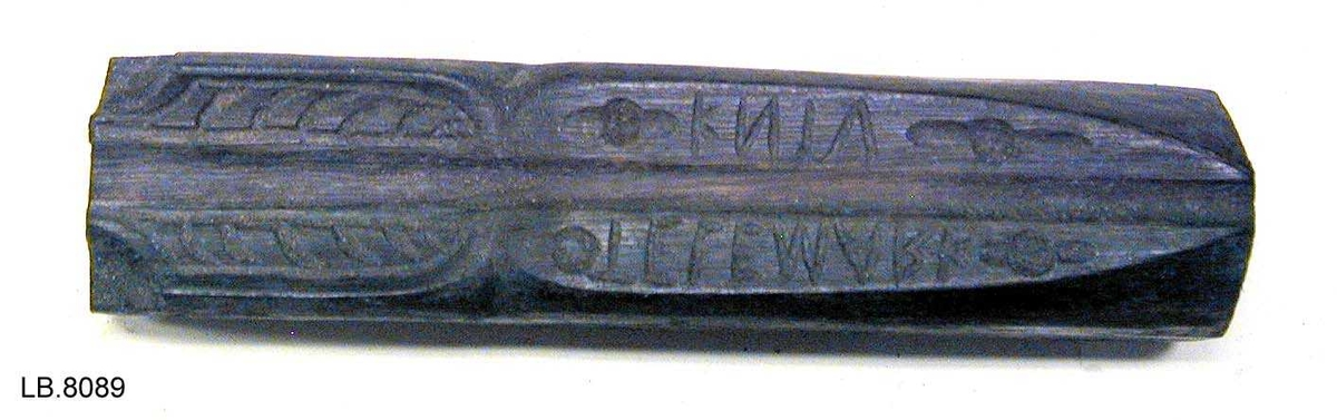 Trykk med påmontera jernplate. Mønster av strekar og tekst.