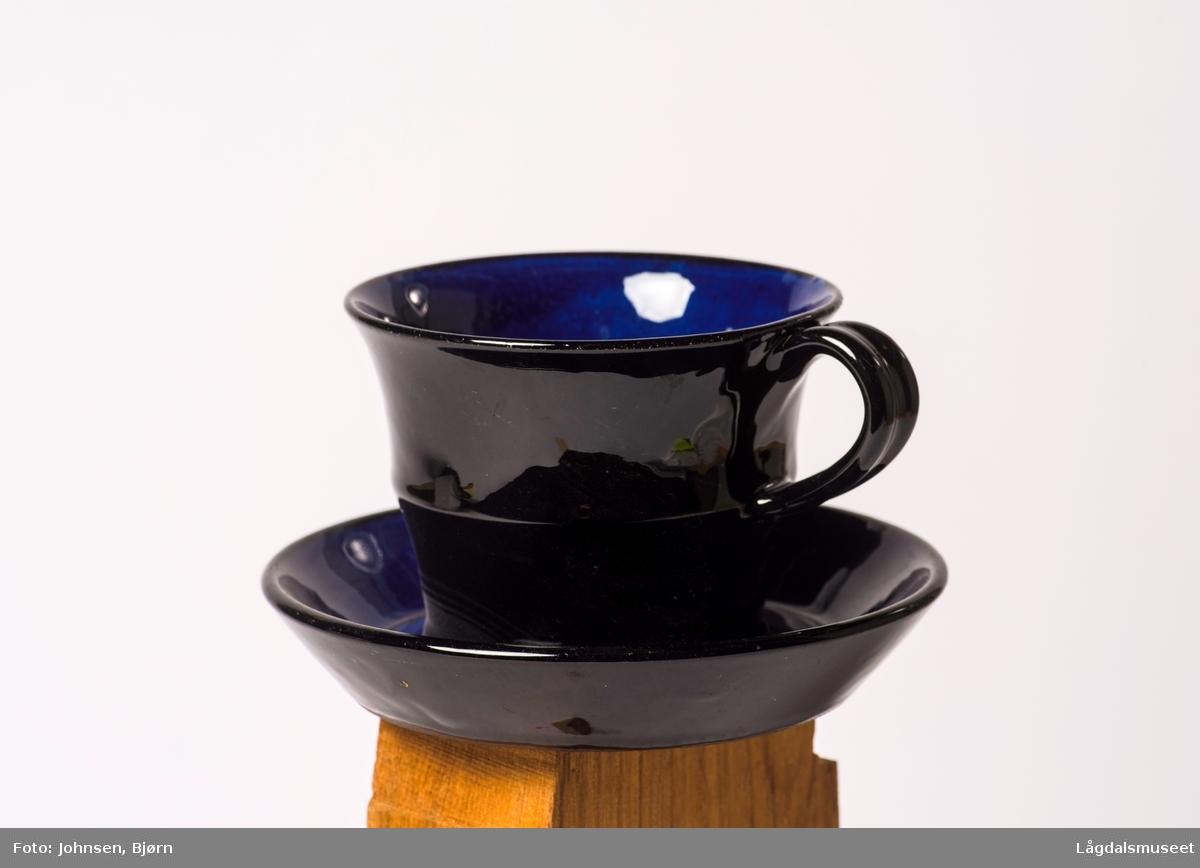 Koboltblå kopp uten dekor, svart utenpå og blå inni.