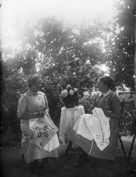 Två kvinnor broderar i trädgården, 1910-talet