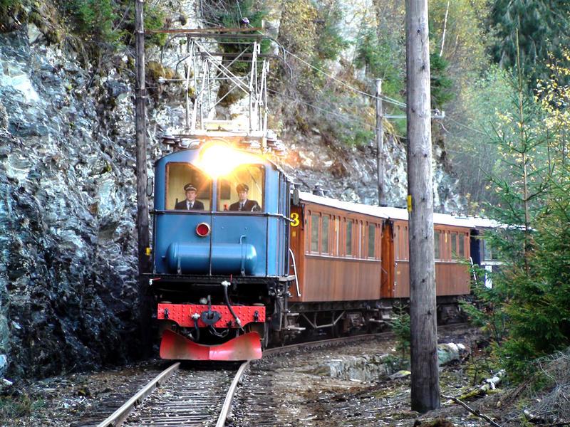 blått lokomotiv og vogner i tre kommer mot på skinnegangen,. Foto/Photo