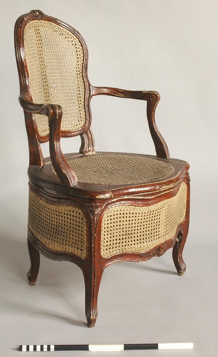Nattstol av brunmålat trä med flätad rotting på ryggbrickan och mellan dubbla sarger på alla fyra sidor. Lätt utsvängda armlän. Lös rottingflätad sits.   Svängda ben, sarger och ramstycke med hålkäl. På ryggen och på  framsidans sarger skuren dekor i form av en blomma med blad. På ryggens baksida en mittslå. Botten utgörs av en låda av furu.