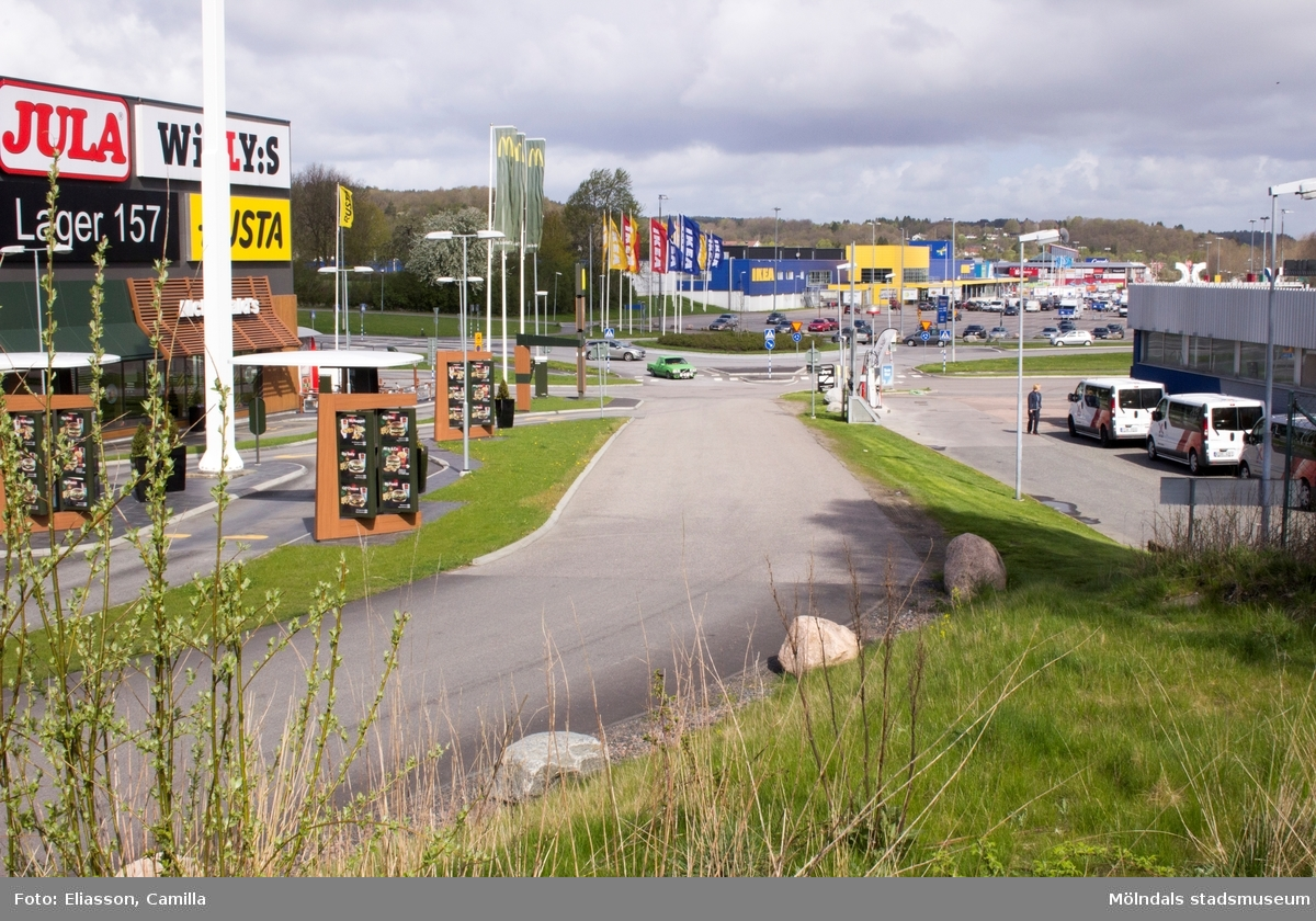 Vy från Ekenleden 1-3 i nordlig riktning mot IKEA. Till vänster ligger Ekens affärscentrum med bl.a McDonald's, som när den byggdes var Sveriges mest moderna och dygnetruntöppna restaurang. På höger sida ligger bensinstationen OKQ8 med tvätt, servicebutik och verkstad.