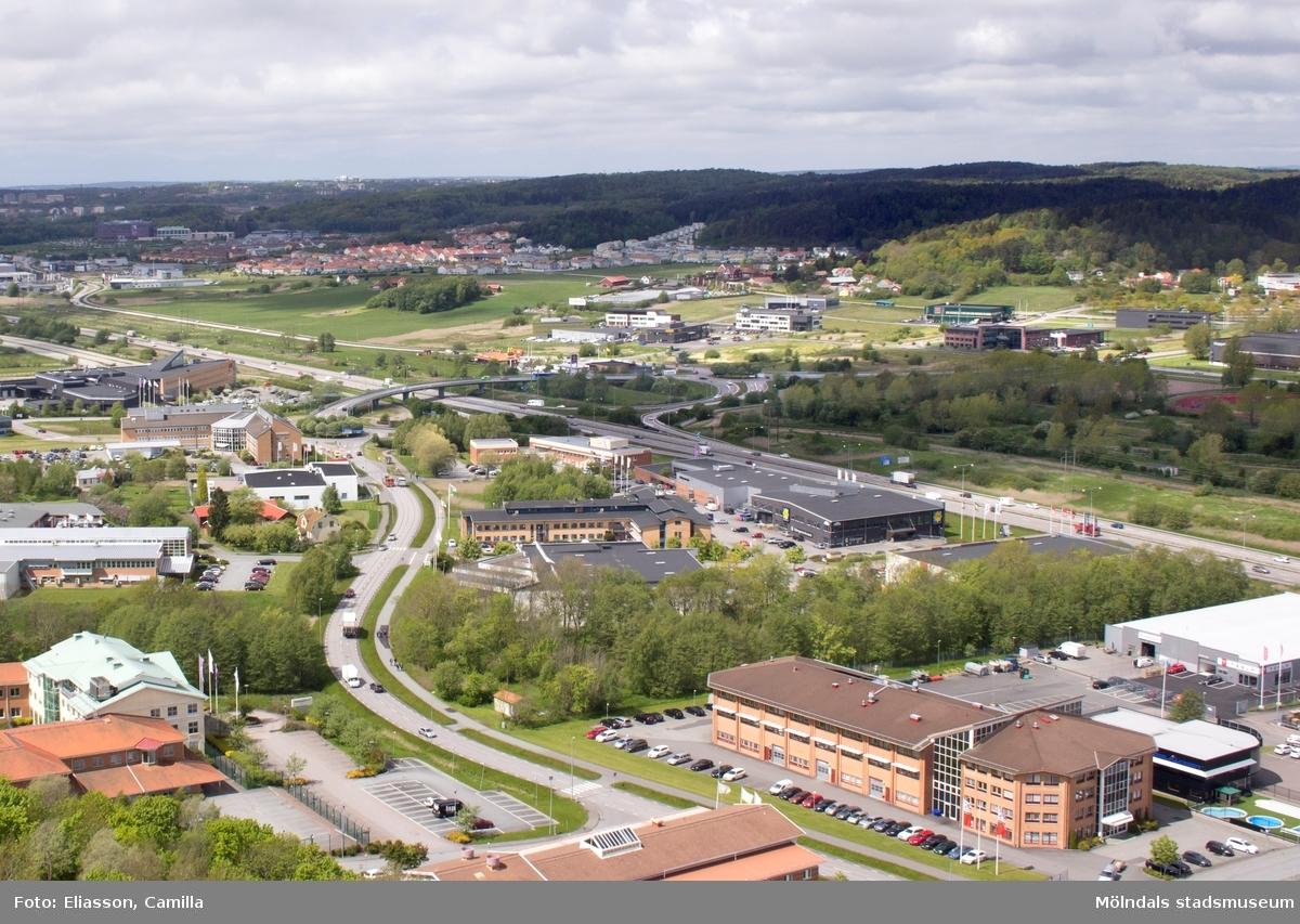 Vy över Fässbergsdalen. I bakgrunden ses mittengården i Fässbergs gamla by (Västergården). Man ser även de tre gårdarna i Fässberg som ännu ligger som i en grön oas, omringade av ny bebyggelse i Eklanda. Den breda motorvägen Söderleden, går mellan Västra Frölunda och Mölndal. Bild tagen från Riskullaverkets skorsten.