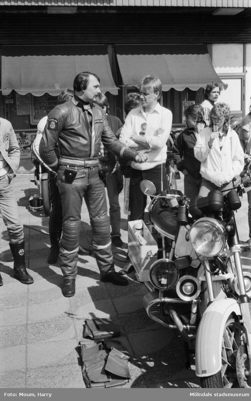 """Kållereds Motorklubb visar upp motorcyklar i Kållereds centrum, år 1984. """"MC-polis Lennart Johansson i samspråk med Mc-klubbens ordförande Dennis Byström.""""  För mer information om bilden se under tilläggsinformation."""