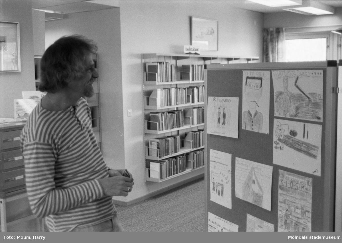 """Ungdomsförfattaren Lasse Ekholm besöker Kållereds bibliotek, år 1984. """"Författaren Lasse Ekholm studerar Kållereds-skolornas illustrationer till personerna i hans ungdomsböcker.""""  För mer information om bilden se under tilläggsinformation."""