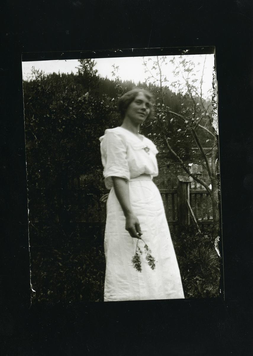 Kvinne iført en hvit kjole med en blomst i hånden. Kvinnen står foran en hekk og en port.
