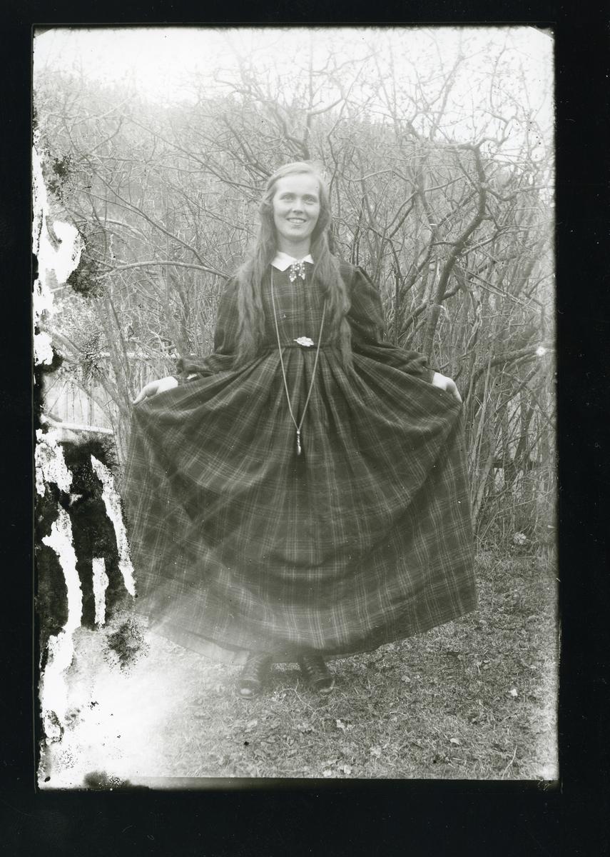 Kvinne holder ut skjørtet på kjolen sin.
