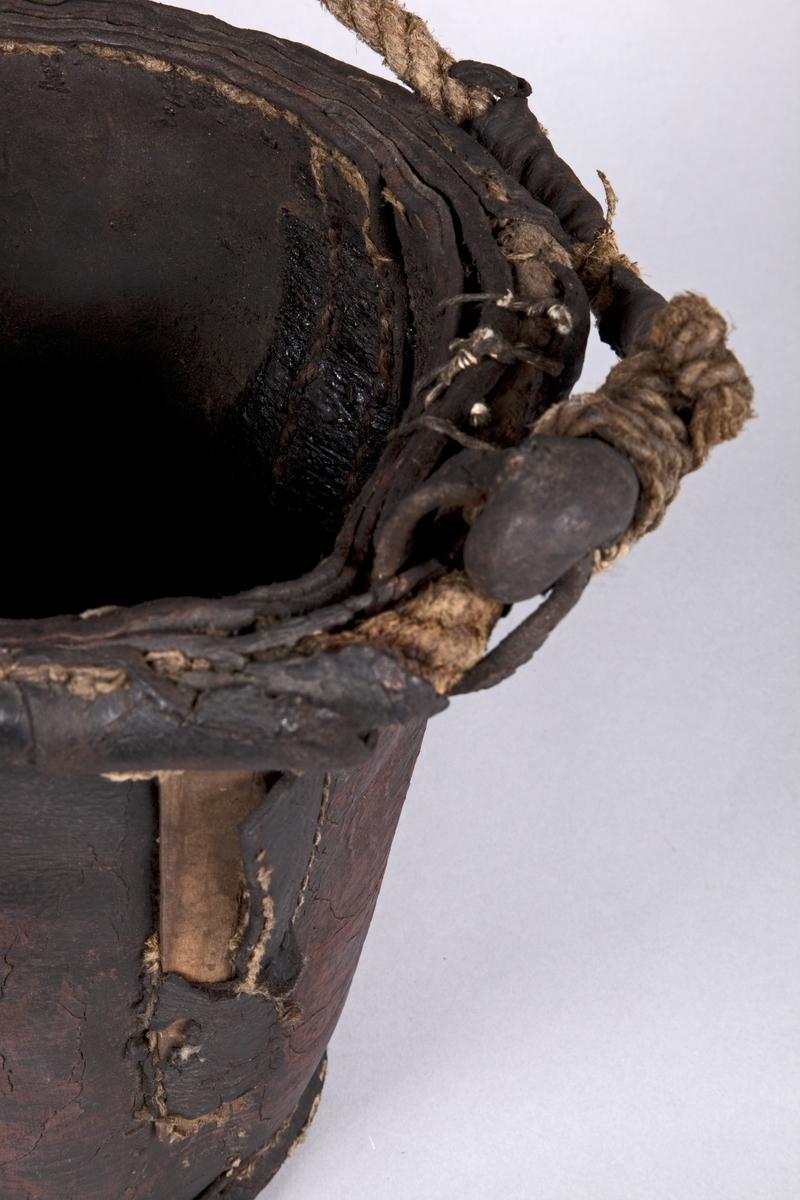 Oval. Satt sammen av tre lærstykker med brede sømfelt imellom. Bøtten smalner nedover mot bunnen. Bøtten har en hank av tauverk festet i to løkker. Hanken har rester av lær rundt tauverket.