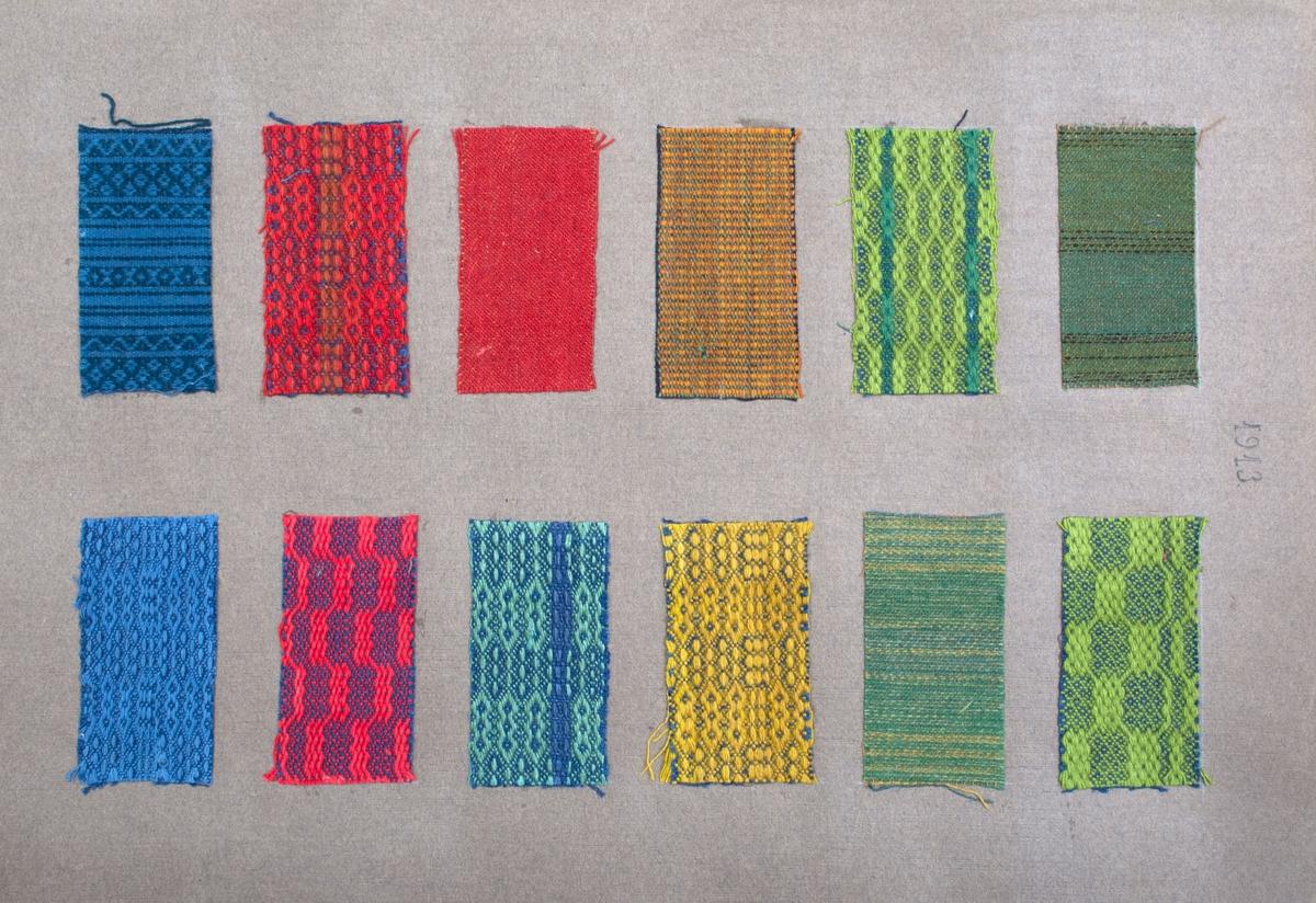 """Stort pappersark med 12 påklistrade tygprover. Varp i bomull, inslag i ull.  Proverna vävda i kypert, kypertdräll, rosengång och rips. Färgerna är i rött, grönt, gult och blått. Text överst på sidan; """"1913""""."""
