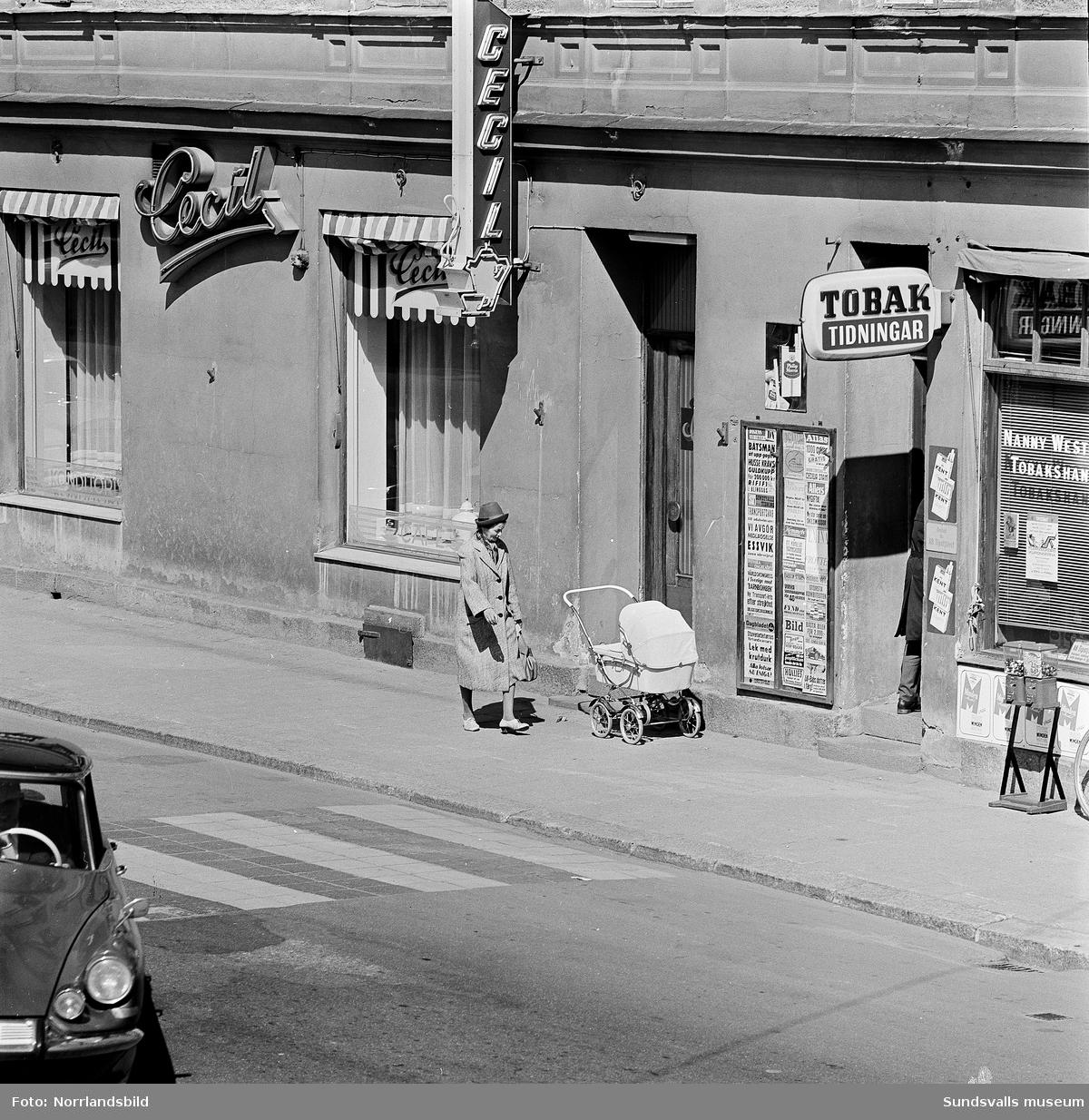 Gatuvy från Köpmangatan. En kvinna och en barnvagn utanför kafé Cecil.