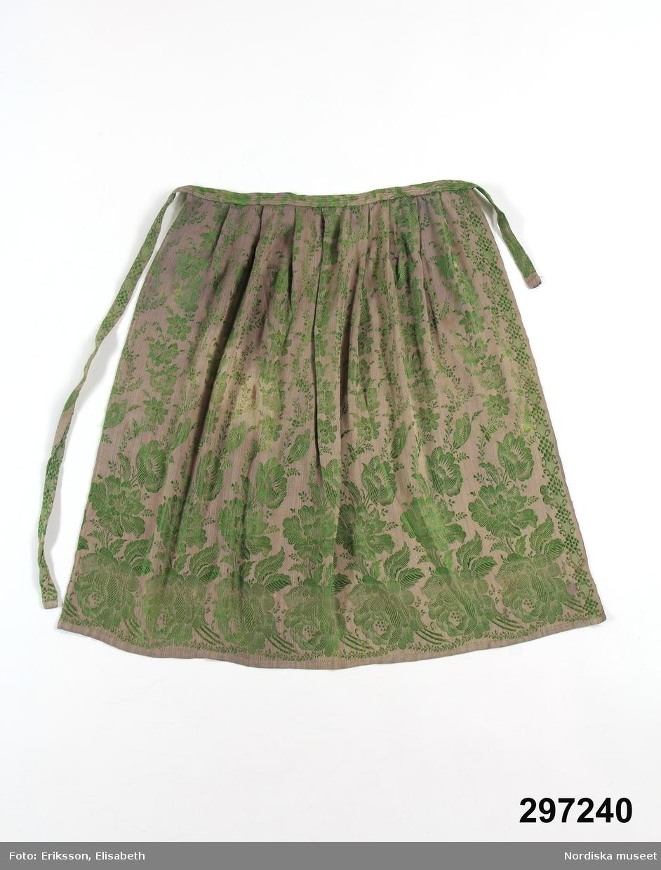 Förkläde av halvsiden med varp av lila bomullsgarn och inslag av grönt silke, i botten varpsatin i den lila bomullen, jacquardvävt blommönster i inslagsflotteringar av det gröna silket, mönstret avpassat för ett förkläde med blomslingor i mitten, bred blombård nedtill och smala kantbårder i nyrokokostil. Upptill breda lagda veck från mitten, linning av tyget 2 cm bred. Linningen skarvad med knytband som klippts från den högra sidans kantbård. Har knutits i vänster sida.  Handsydda fållar nedtill och i höger sida, till vänster stadkant. Anm. Den lila bomullen urblekt till grålila, ursprungsfärgen syns på avigsidan. Liknar i mycket halskläden från samma tid.  Kommer från gården Nyby i Vik sn. Förklädet har sannolikt tillhört Per Larssons ( f. 1850) mor, snarare än hustrun Kristina  som föddes först 1866. /Berit Eldvik 2012-04-11