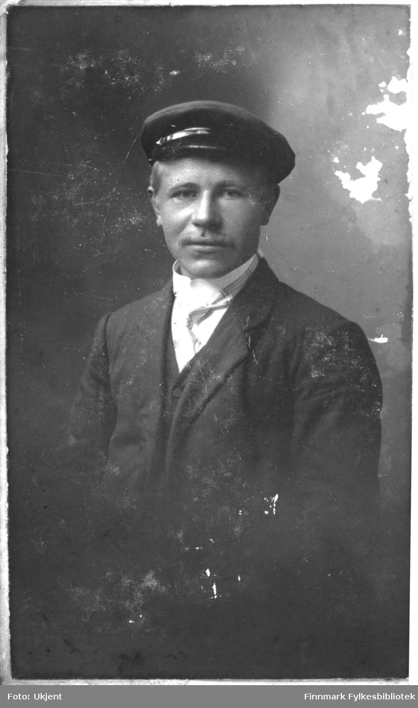 Et portrett av Gustav Gustavsen fra Sommernes, Nuvsvåg. Han drev handel og fiskeri, og eide/arbeidet på et sildnotbruk. Han er kledd i dress: jakke, skjorte med høy krage og slips. På hodet har han en hatt.
