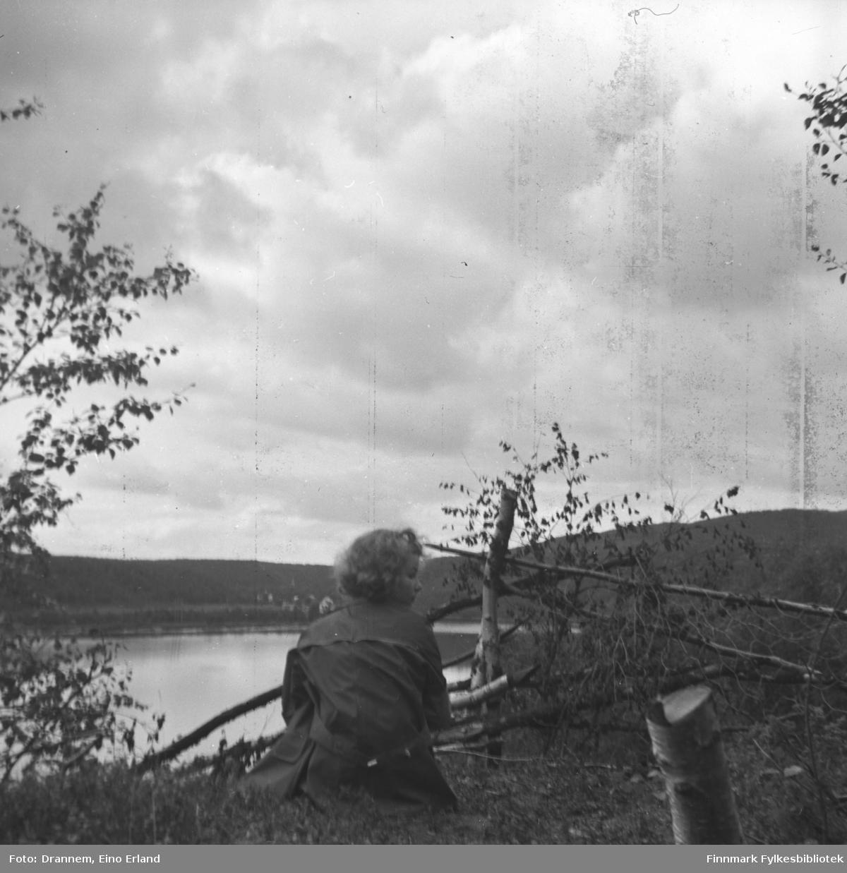 Turid Karikoski sitter innenfor en innhengning i Neiden.