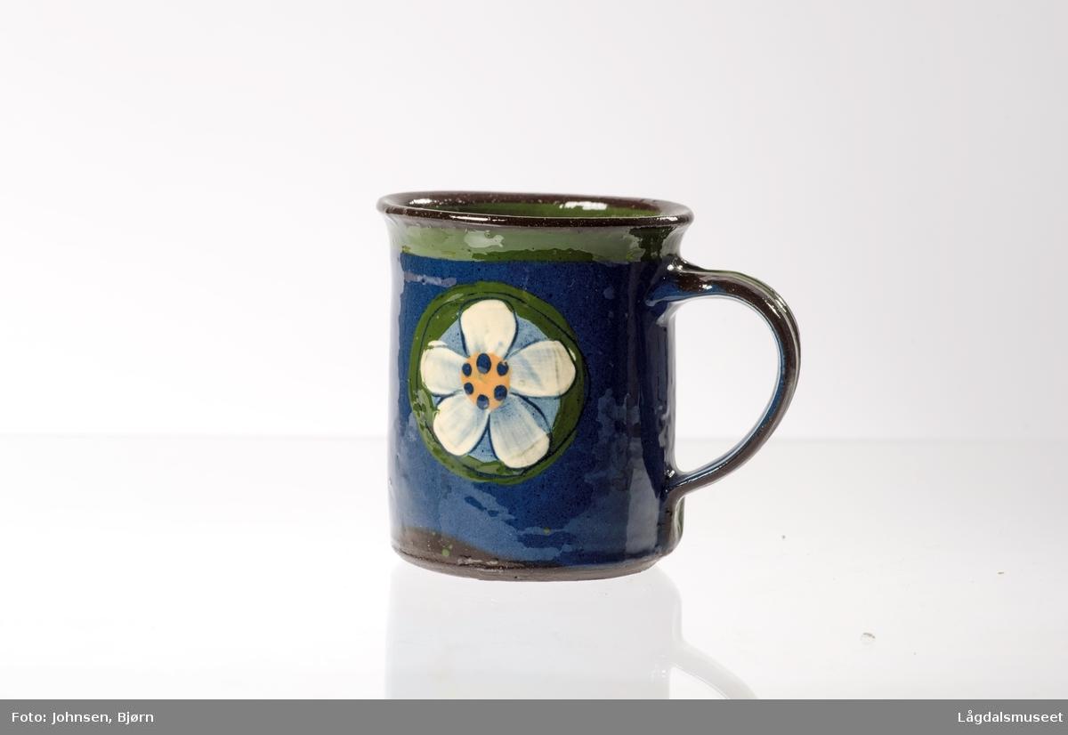 """Koppen er dekorert med det kjente motivet """"hvit blomst""""."""