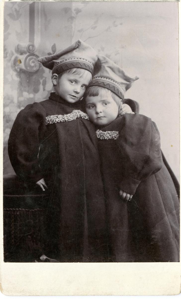 To barn iført lue og lange kjoler.