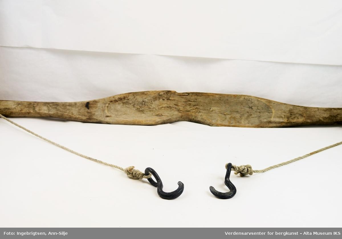 En lang bjelke med en konkav bue i midten. I hver ende er det festet tau med krok.