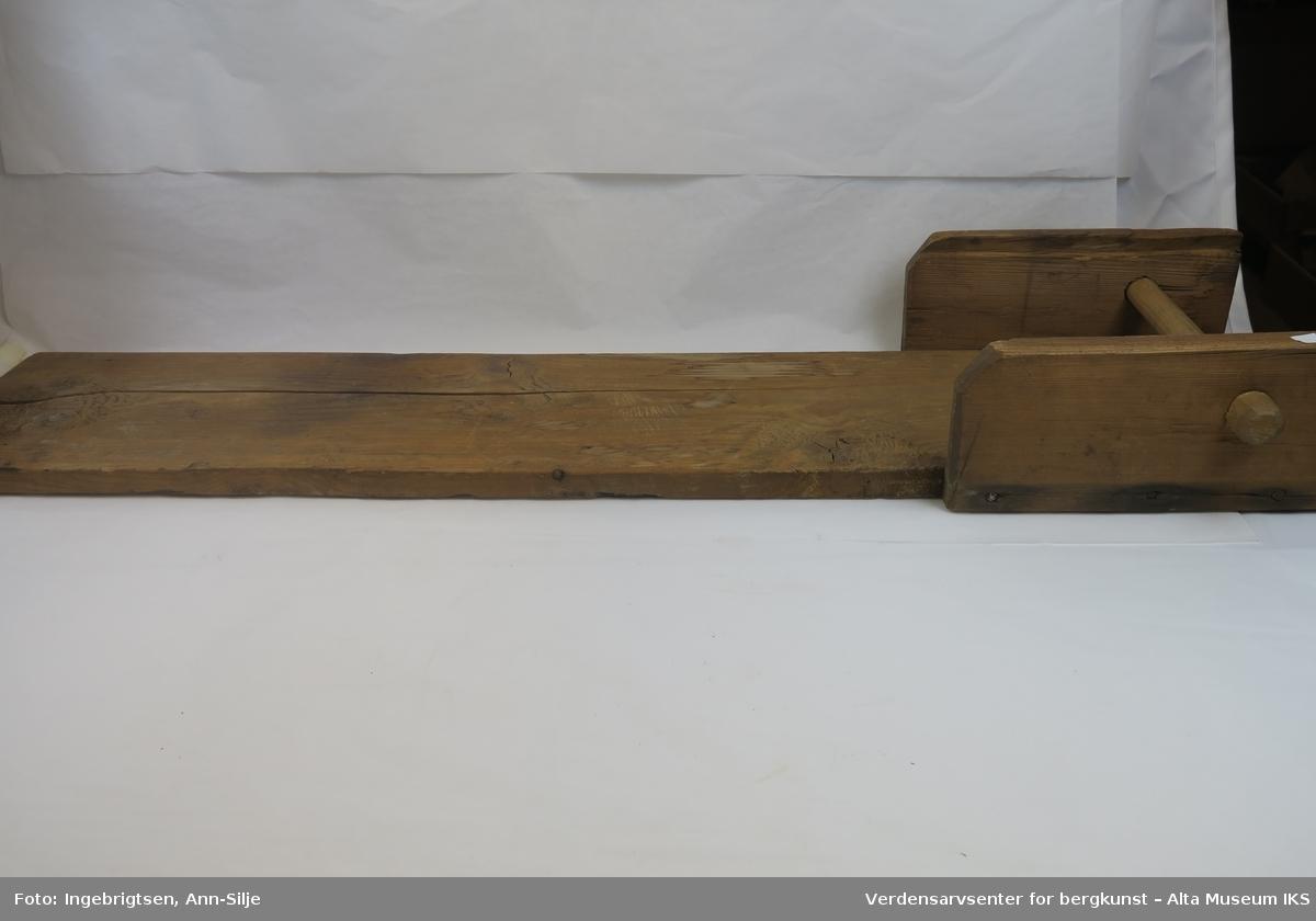 Lang umalt plate. I den ene enden er det påmontert en karde. Brukt til grovkarding av ull.